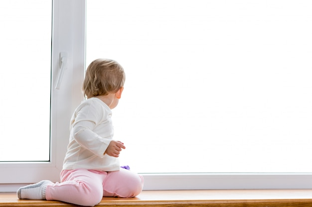A criança senta e olha para fora da janela