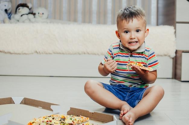 A criança senta no chão e come pizza bem apetitosa e gulosa, de bermuda e camiseta