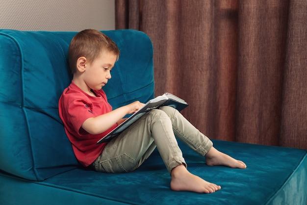 A criança senta no sofá e aprende a ler seu primeiro conto de fadas.