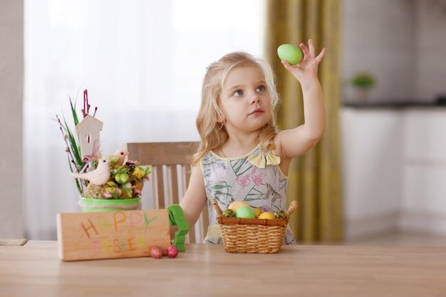 A criança senta-se à mesa de férias com uma cesta de ovos de páscoa. segura um ovo na mão e considera