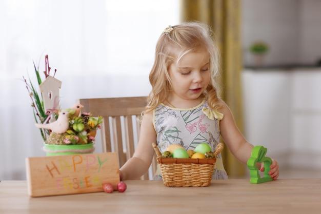 A criança senta-se à mesa de férias com uma cesta de ovos de páscoa.