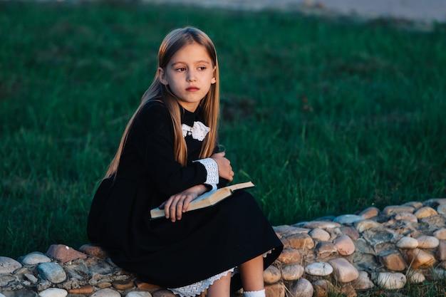 A criança senta-se em uma cerca de pedra e segura um livro, afastando-se e pensando.