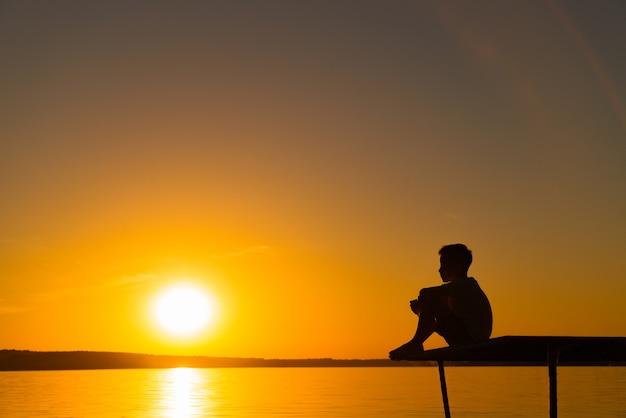A criança senta-se em uma ponte e parece no rio ao pôr do sol. um menino é relaxar perto do lago