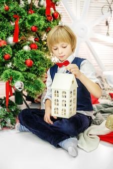A criança senta-se na árvore de natal e brinca