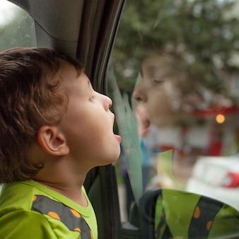 A criança senta-se no carro sozinha