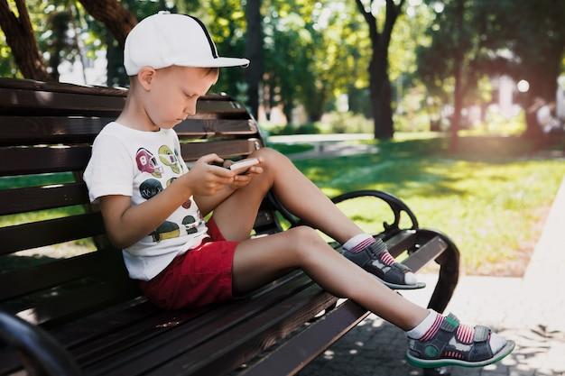 A criança senta-se no parque em um banco com um gadget. as crianças usam gadgets. retrato de um menino bonito no sol poente. um menino joga um jogo em um telefone celular.