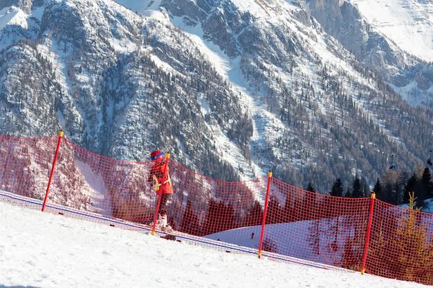A criança sobe o travolador na pista de esqui atrás de uma rede de proteção vermelha