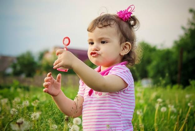 A criança sopra bolhas. foco seletivo. natureza.