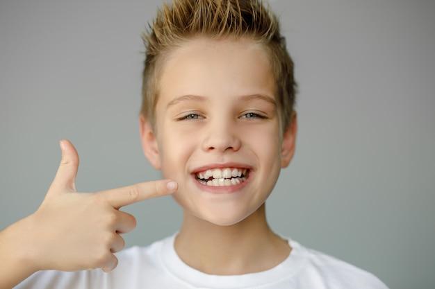 A criança sorri e mostra os dentes irregulares. medicina dentária e saúde