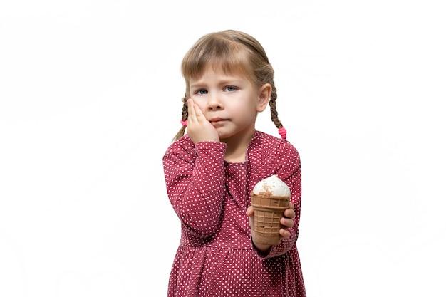A criança tem dor de dente enquanto toma sorvete. sensibilidade dos dentes ao frio.