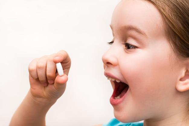 A criança tem na mão um comprimido branco oval e quer engoli-lo com alegria. medicamentos e vitaminas sintéticas.