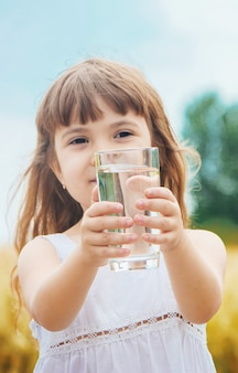 A criança tem um copo de água nas mãos. foco seletivo.
