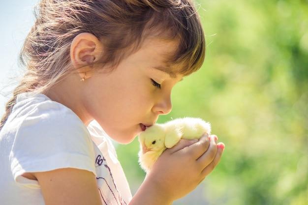 A criança tem um frango nas mãos.
