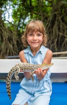 A criança tem um pequeno crocodilo nas mãos.