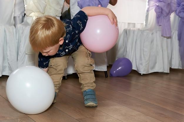 A criança tenta levantar o balão da mesa de banquete crianças em festa em restaurante