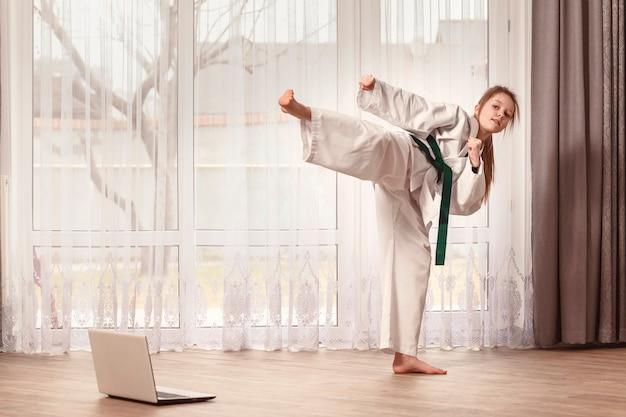 A criança treina em casa na frente de um laptop