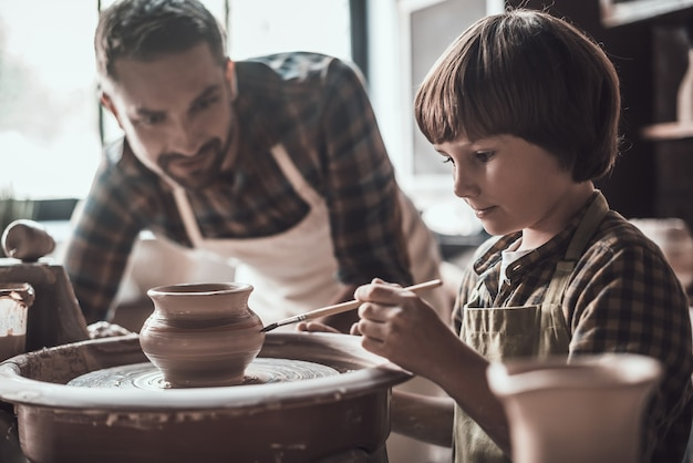 A criatividade está em suas veias. garotinho desenhando em um pote de cerâmica na aula de cerâmica, enquanto um homem de avental está perto dele