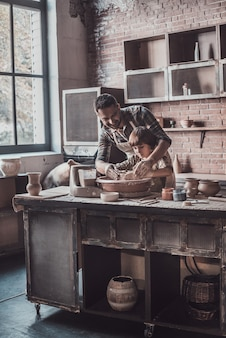A criatividade está em suas veias. jovem alegre e garotinho fazendo potes de cerâmica na aula de cerâmica