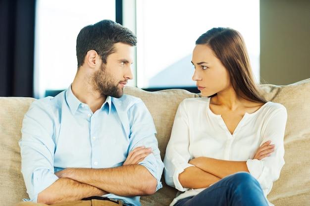 A culpa é tua! jovem casal furioso olhando um para o outro e mantendo os braços cruzados enquanto está sentado perto um do outro no sofá