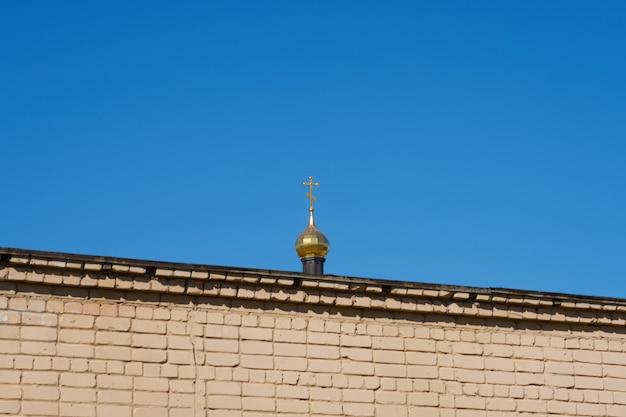 A cúpula da igreja atrás da parede de tijolos contra o céu azul claro.