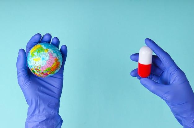 A cura para a pandemia global. mão de um médico em luvas de látex segura um globo e uma cápsula em um fundo azul. conceito médico
