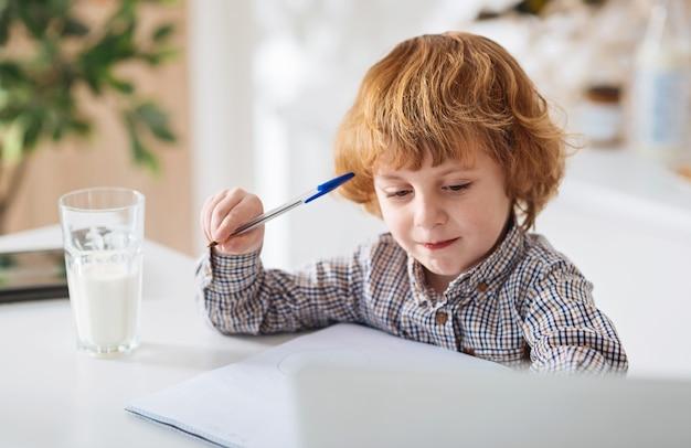 A curiosidade é a chave. criança adorável e admirável sentada à mesa da cozinha e escrevendo notas enquanto bebe um copo de leite