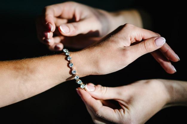A dama de honra ajuda a colocar uma pulseira no braço para a noiva. noiva colocando joias, foco na pulseira. preparação nupcial para a cerimônia de casamento.