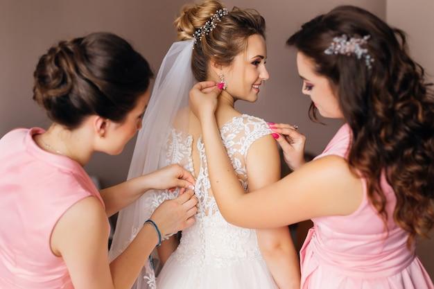 A dama de honra ajuda a noiva com o vestido