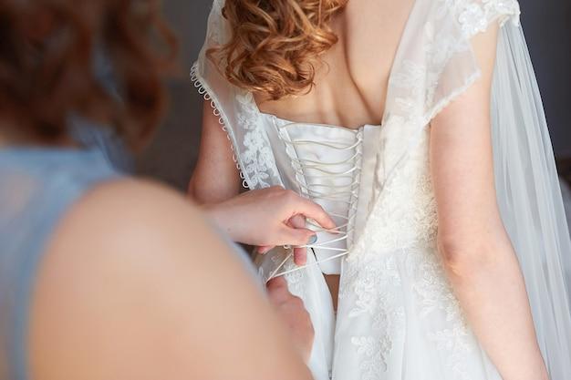 A dama de honra ajuda a vestir a noiva no dia do casamento.