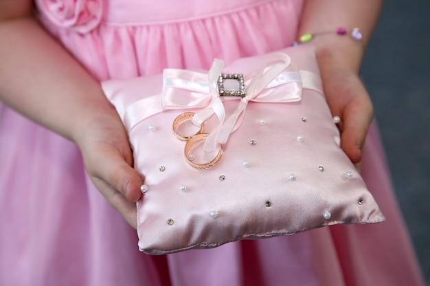 A dama de honra segura uma almofada decorativa com anéis de casamento de ouro