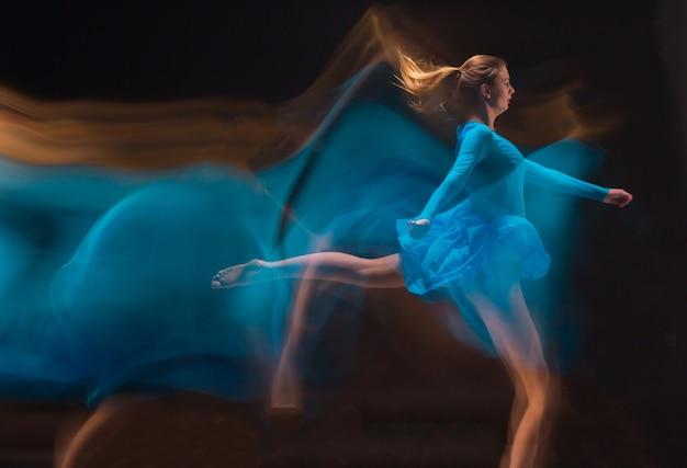 A dança artística foto-emocional de uma linda garota de vestido azul