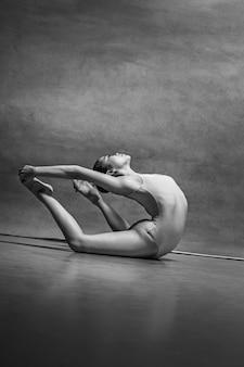 A dançarina de balé feminina posando sobre cinza