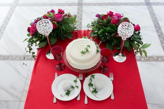 A decoração do casamento - mesa de casamento para dois. bolo branco, flores, copos de cristal na mesa vermelha. vista de cima.