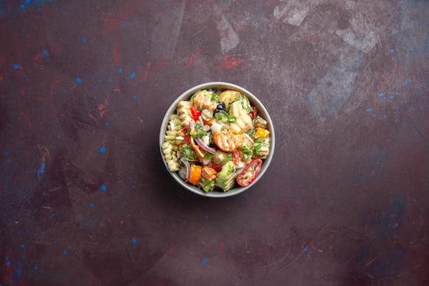 A deliciosa salada de vegetais da vista de cima consiste em tomates, azeitonas e pimentões em um fundo escuro, dieta saudável, refeição leve, salada