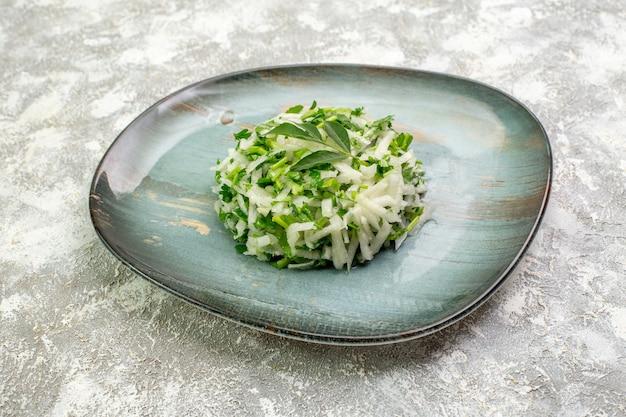 A deliciosa salada frontal consiste em verduras e repolho dentro do prato na superfície branca