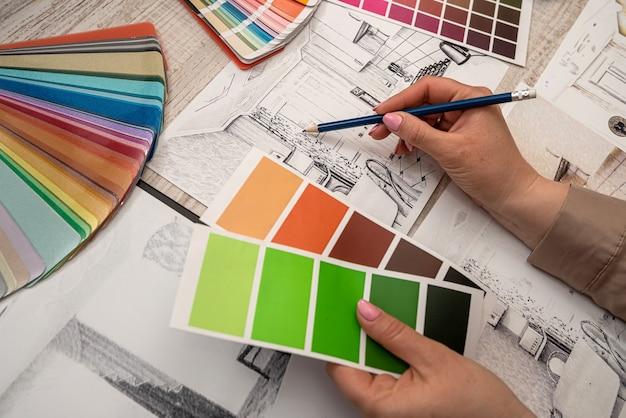 A designer de interiores feminina escolhe a cor na paleta, trabalhando com um esboço de casa no escritório