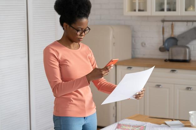 A designer milenar de uma mulher remota tira uma foto de um documento no smartphone para enviar o plano ao cliente ou chefe