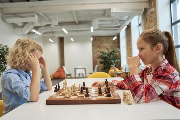 A determinação concentrou menino e menina olhando um para o outro enquanto jogavam xadrez sentados juntos