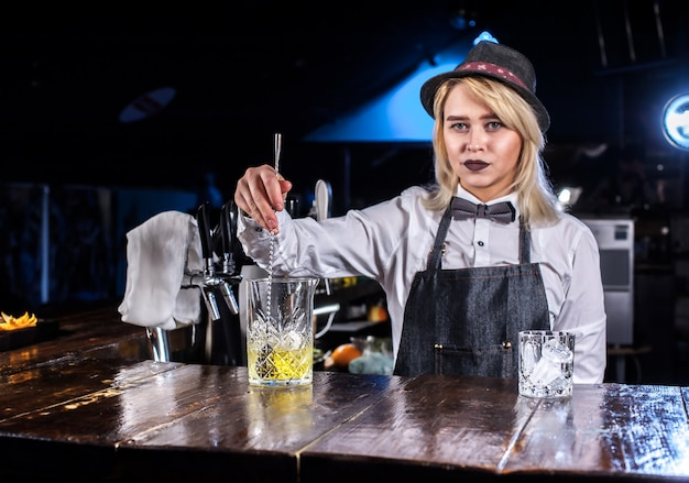 A doce menina bartending faz um show criando um coquetel na boate