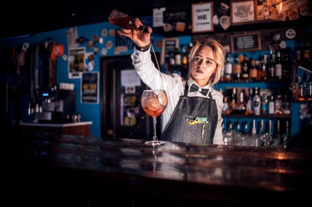 A doce mulher taberna demonstra o processo de fazer um coquetel em pé perto do balcão do bar em uma boate
