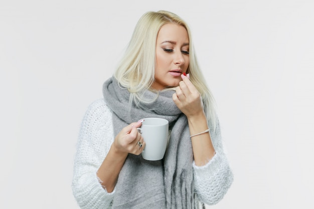 A doença mulher loura nova bonito envolveu o lenço que tem a dor de cabeça, tocando em seu templo e em olhos fechados, close up. frio, vírus, enxaqueca, conceito de temporada de gripe.