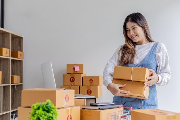 A dona da loja online segura duas caixas de pacotes, ela verifica o saldo do pedido e prepara para a entrega, um pacote para embalar a mercadoria. venda online e conceitos de compras online.