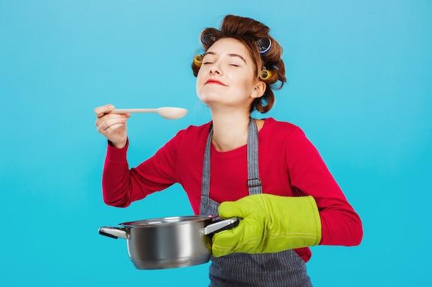 A dona de casa agradável cheira e prova a sopa caseira na cozinha