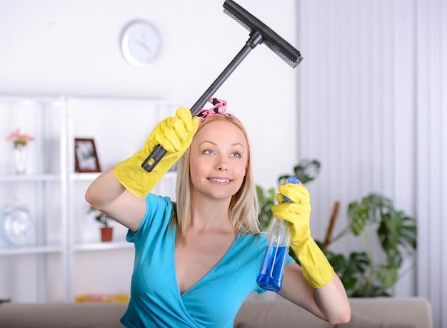 A dona de casa bonita limpa uma janela em casa.