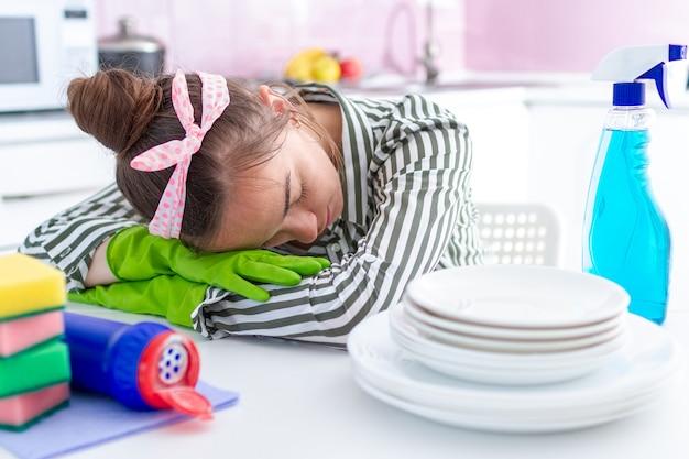 A dona de casa cansada e adormecida adormeceu e descansou em cima da mesa por causa do cansaço da limpeza da primavera e das tarefas domésticas difíceis