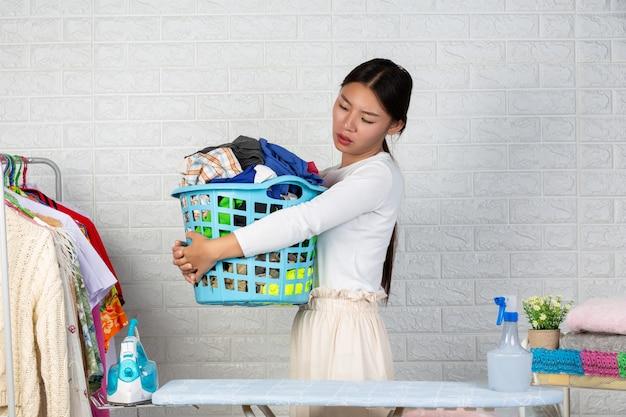 A dona de casa cansada está cansada das roupas da cesta com um tijolo branco.