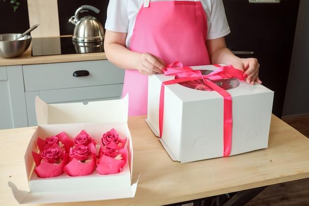 A dona de casa chefe confeiteira está embalando bolo e cupcakes nas caixas conceito de entrega de sobremesas