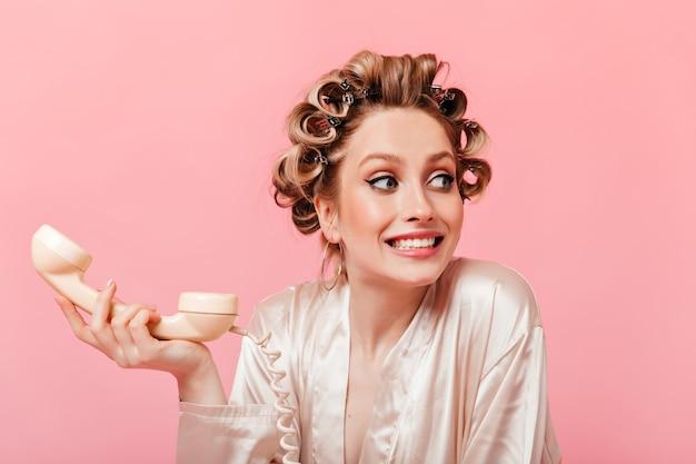 A dona de casa com blusa de seda se sente estranha e segura o telefone fixo na parede rosa