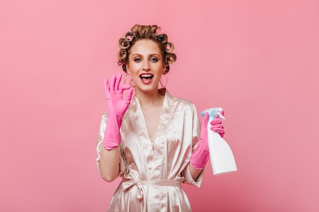 A dona de casa com luvas cor-de-rosa segura o limpador de vidros e mostra o sinal de ok