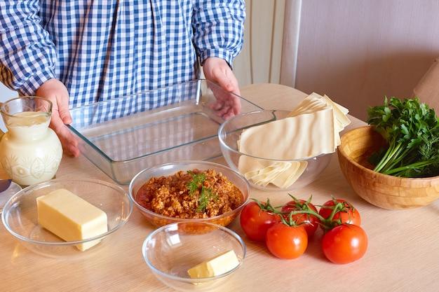 A dona de casa cozinha lasanha de carne na cozinha. comida caseira